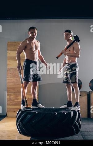 Zwei Männer stehen auf Reifen- und Holding asledgehammer - Stockfoto