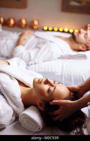 glückliche junge schöne Paar genießen Kopf massage im spa - Stockfoto