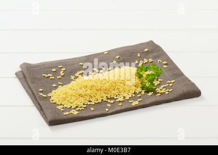 Stapel der Ungekocht alphabet Nudeln auf grauer Unterlage - Stockfoto