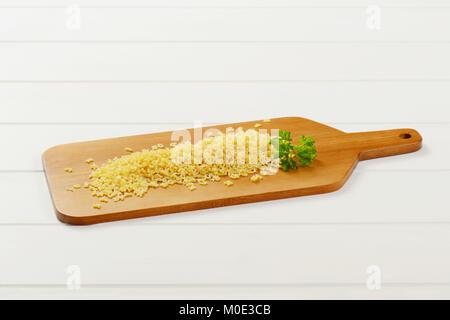 Heap ungekochten Alphabet Nudeln auf Holz Schneidebrett - Stockfoto