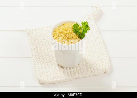 Tasse ungekochter Alphabet Nudeln in White Table mat - Stockfoto
