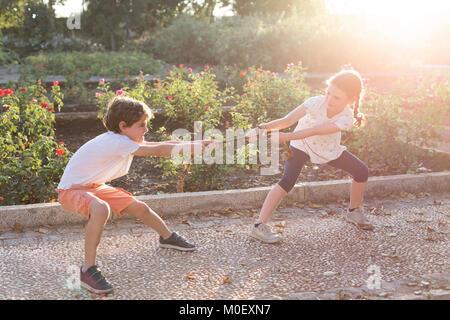 Jungen und Mädchen im Garten ziehen ein Seil - Stockfoto