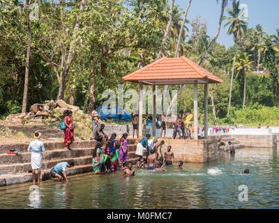 12/30/2017. Verkala, Kerala, Indien. Kinder und Erwachsene baden in einem alten Brunnen in der Mitte der Stadt. - Stockfoto