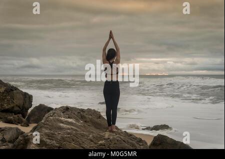 Frau Yoga auf den Felsen am Meer, ständigen Lotus Position. - Stockfoto
