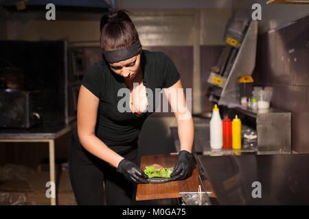 Frau Koch in der Küche vorbereiten eines Hamburger Sandwich - Stockfoto