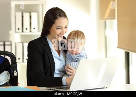 Glückliche Mutter arbeiten auf der Linie mit einem Laptop ihr Baby Sohn Holding im Büro - Stockfoto