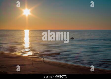 Sonnenuntergang an einem Sandstrand mit einem Dock, offene Meer. Lido di Jesolo, Italien. - Stockfoto