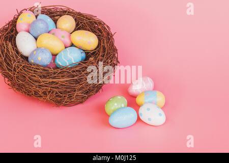 Bunte Ostereier im Nest auf dem rosafarbenen Pastelltönen Hintergrund mit dem Raum. - Stockfoto