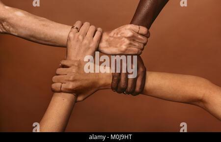 Vier unterschiedlichen Frauen, die sich in jeden anderen Handgelenken in einem Kreis. Blick von oben auf die weibliche - Stockfoto