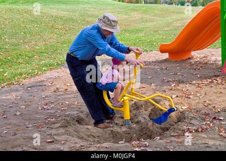 Ein Großvater, der in einem Park mit seiner schönen Enkelin - Stockfoto