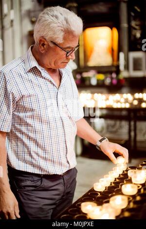 Älterer Grauhaariger leuchtet ein vollgültiges Kerze im Köner Dom, Köln, Nordrhein-Westfalen, Deutschland - Stockfoto