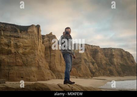Mann, auf Felsen, die von der zerklüfteten Küste ein Foto. - Stockfoto