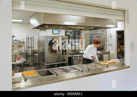 Ein catering Assistent bereitet die Schule Mittagessen in einer neuen Grundschule in London, UK. - Stockfoto