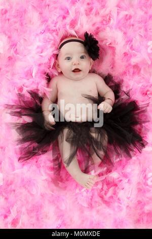 Schönen wurf Mädchen, 4 Monate altes Baby Mädchen in Tutu auf rosa Federn - Stockfoto
