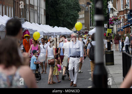 Menge Szene am Marlyebone Sommer Fayre Marlyebone Food Festival in London an einem sonnigen Tag mit gelben Luftballons - Stockfoto