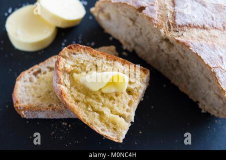 Spezialität Butter schmelzen auf warmen Artisan Brot auf einem schwarzen Hintergrund. - Stockfoto