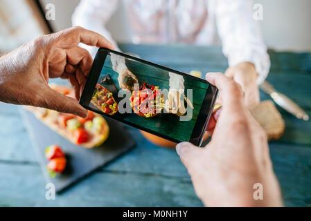 Nahaufnahmen der Hände des Menschen, ein Foto mit dem Handy Salat von Tomaten, Granatapfel, Papaya und Oliven, mit - Stockfoto
