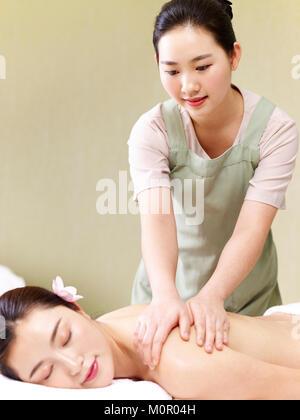 Jungen asiatischen Masseur durchführen Massage auf Frau in Spa Salon. - Stockfoto
