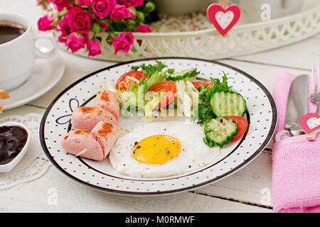 Frühstück am Valentinstag - Spiegelei in Herzform, Toast, Würstchen und frischem Gemüse. Tasse Kaffee. Englisches - Stockfoto