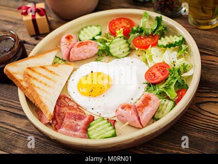 Frühstück am Valentinstag - Spiegelei in Herzform, Toast, Würstchen, Speck und frischem Gemüse. Englisches Frühstück - Stockfoto