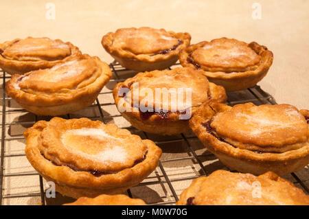 Frisch zubereitete hausgemachte Torten Gehacktes, heiß aus dem Ofen und Abkühlen am Draht Rack, mit einer Prise - Stockfoto
