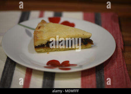 Essen Fotografie mit einem hausgemachten Gebäck und Obst Scheibe der englische Prediger tart auf einem roten und weißen Blumen Platte mit Tischdecke Hintergrund
