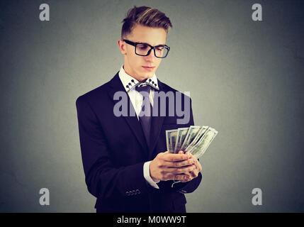 Jungen ehrgeizigen Mann in Anzug zählen Dollarscheine in den Händen auf Grau posieren. - Stockfoto