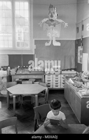 """Dorf Grundschule 1970s England. Kleiner Junge in und nicht gestattet, außerhalb zu einem """"richtigen Charlie' zu - Stockfoto"""