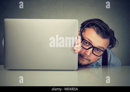 Junge müde Mann in Brillen versuchen hinter Laptop suchen Angst vor Wettbewerb zu verstecken. - Stockfoto