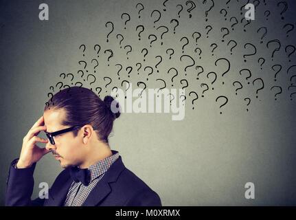 Elegante Mann in Brillen rieb Stirn mit Fragezeichen auf grauem Hintergrund. - Stockfoto