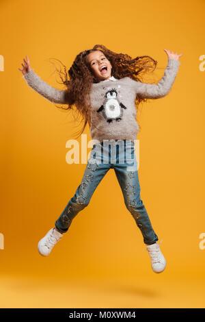 Bild von Angeregten glücklichen kleinen Mädchen auf gelben Hintergrund suchen Kamera isoliert springen. - Stockfoto