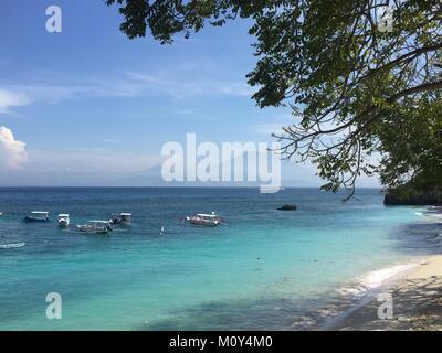 Blick auf das Meer, Fischerboote, weiß San Beach und die Silhouette von Balis Vulkane im Hintergrund Stockfoto