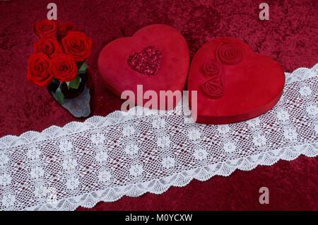 Valentine Hintergrund, rote Leathered Herz geformten Süßigkeiten, mit frischen Rote Rose Bouquet auf rotem Hintergrund, - Stockfoto