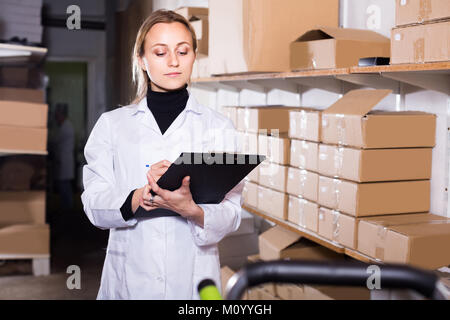 Lächelnd europäischen Arbeiterin Transport Warenkorb Karton Fälle in Storage - Stockfoto