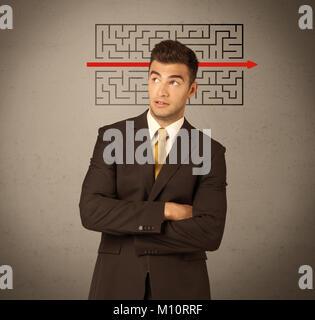 Ein junger hübscher business Person, die Mimik und die Lösung Labyrinth mit roter Pfeil vor Löschen, leere Beton - Stockfoto