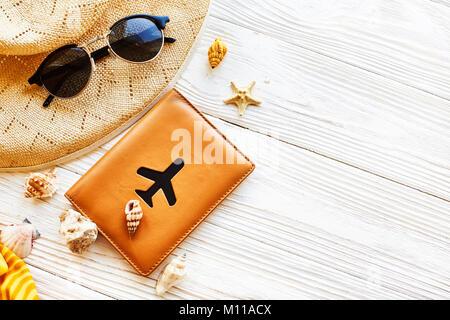 Sommer Urlaub Konzept flach. gelben Hut, Sonnenbrille und Muscheln und Reisepass mit dem Flugzeug auf weißen Holzmöbeln - Stockfoto