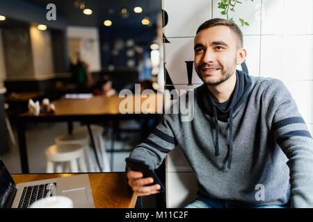 Nahaufnahme der männlichen Hände halten und den Einsatz moderner smart phone im Cafe Shop. Mann Senden neuer Nachrichten - Stockfoto