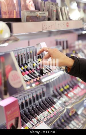 Nahaufnahme einer Frau Hand, Lipgloss, Lippenstift Tester in einem japanischen Make-up und Schönheit Produkt store - Stockfoto