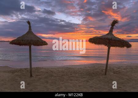 Reetgedeckte Sonnenschutz Sonnenschirme am Strand von S'Arenal, Palma de Mallorca, Mallorca, Balearen, Spanien - Stockfoto