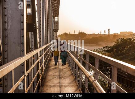 Zwei Mädchen zu Fuß in Eisenbahnbrücke nach der Arbeit auf dem Weg nach Hause bei Sonnenuntergang, Agra, Indien Stockfoto