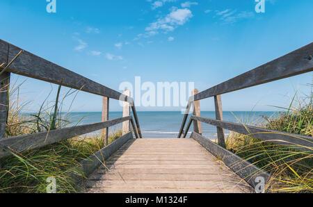 Blick auf die Ostsee mit Dünen und blauer Himmel von einer hölzernen Pfad zum Meer im Sommer. - Stockfoto