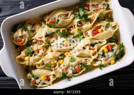 Conchiglioni Pasta gefüllt mit Huhn, Pilzen und Gemüse close-up in einer Auflaufform auf einen Tisch. Horizontal - Stockfoto
