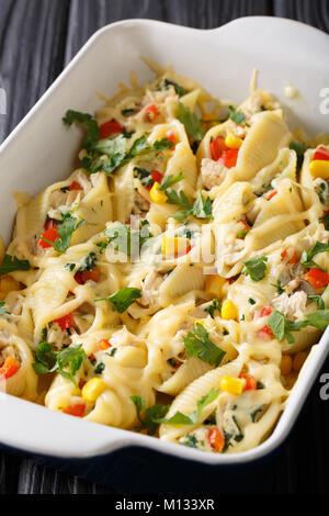 Gebackene Nudeln conchiglioni mit Huhn, Pilzen und Gemüse Makro in einer Auflaufform auf einem Tisch. Vertikale - Stockfoto