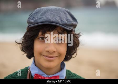 Kopf und Schultern Porträt einer Brünette Junge mit langen Haaren, mit flacher Deckel und red Bow Tie - Stockfoto