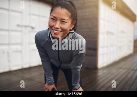 Lächelnd asiatische Frau in Sportkleidung stand mit den Händen auf die Knie, während sie eine Pause von einem Lauf - Stockfoto