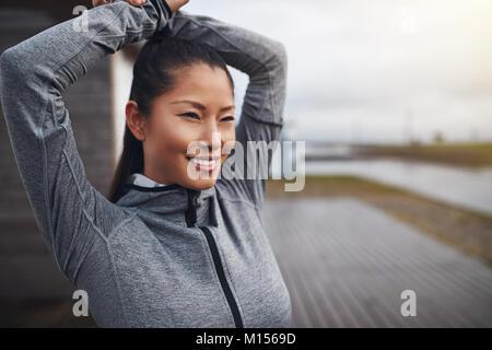 Lächelnde junge asiatische Frau in sporstwear allein draußen mit ihren Armen, bevor sie für einen Lauf an einem - Stockfoto