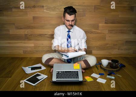 Ernsthafte junge Mann arbeitet in lustiger Kleidung und macht wichtige Hinweise. Eine barfuß Geschäftsmann sitzt - Stockfoto