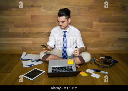 Ernster junger Mann in lustiger Kleidung mit Smartphone und Tasse Kaffee arbeitet mit Projekt. Eine barfuß Geschäftsmann - Stockfoto