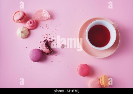 Süße französische Macarons und Baisers auf rosa Hintergrund. - Stockfoto