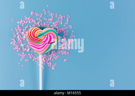 Liebe und Valentinstag Konzept. Herz Sweet Lollipop Candy mit Blume Glitter lag auf blauem Hintergrund - Stockfoto